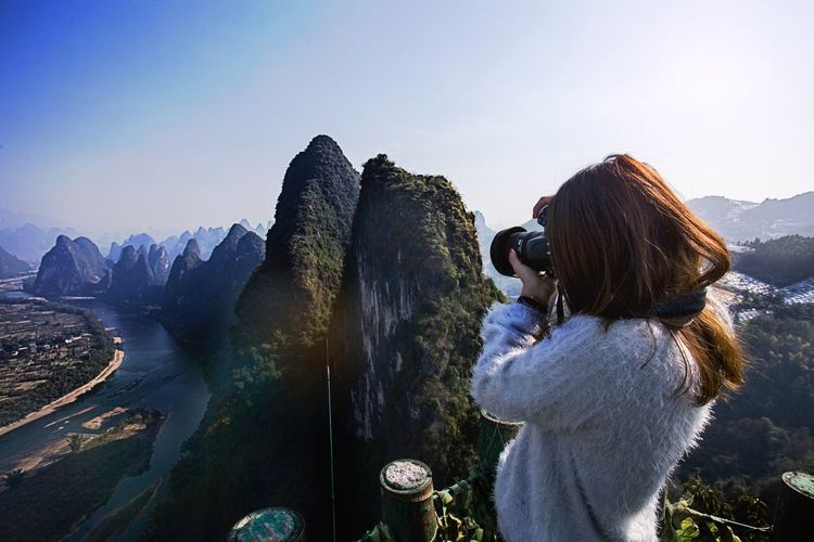 Woman photographing mountains against sky