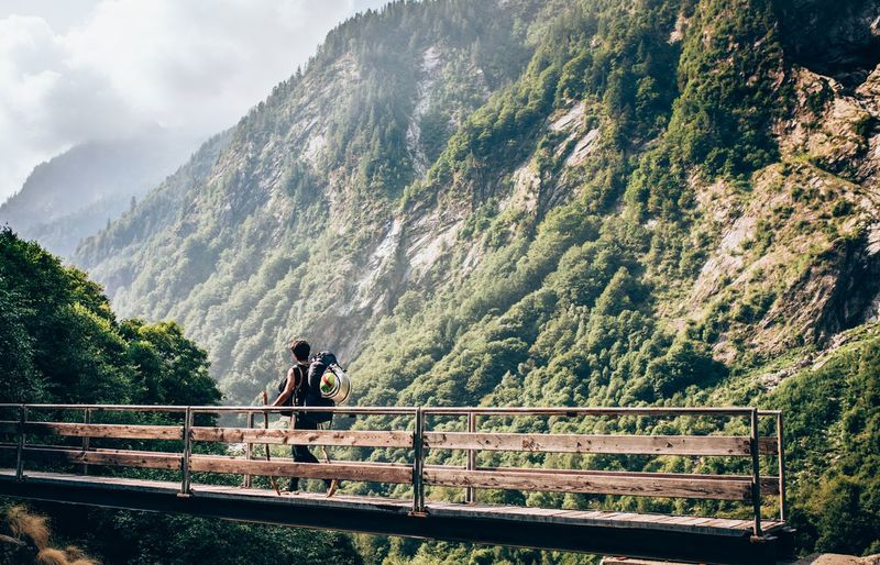 Rear View Of Hiker Walking On Bridge Against Mountains