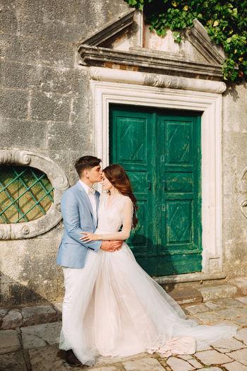 Bridegroom embracing while standing by door outdoors