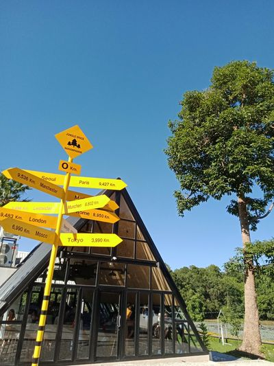 Low angle view of yellow sign against clear sky