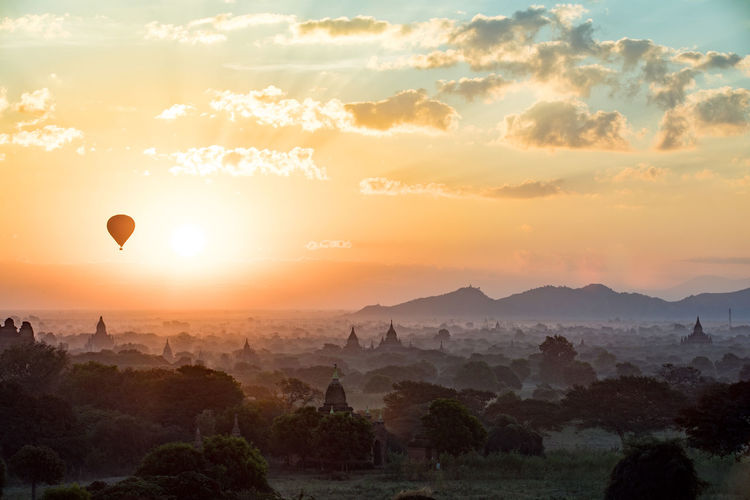 Air Vehicle Balloon Beauty In Nature Cloud - Sky Environment Hot Air Balloon Idyllic Landscape Mountain Nature No People Non-urban Scene Orange Color Outdoors Plant Scenics - Nature Sky Sun Sunset Tranquil Scene Tranquility Tree
