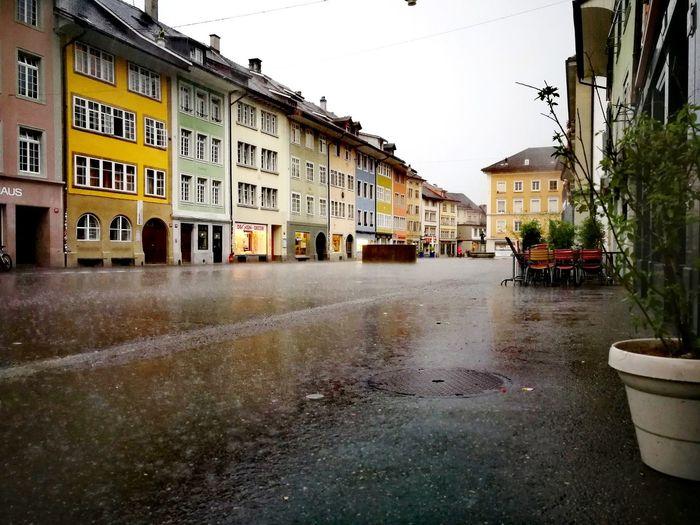 Wet street by buildings against sky in city