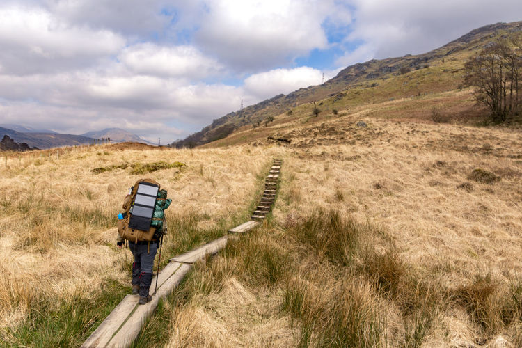 Rear View Of Hiker Walking On Boardwalk Against Sky
