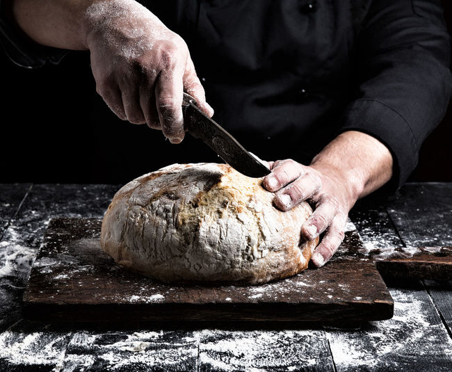 Close-up of person cutting bread with knife at counter