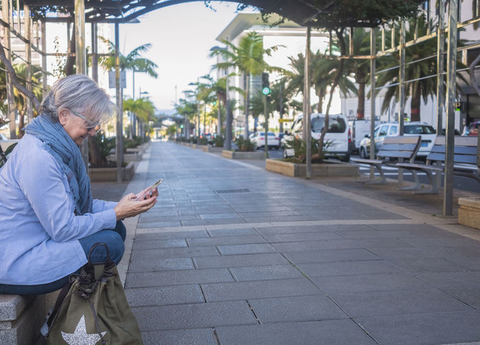 Side view of senior woman using phone while sitting by walkway