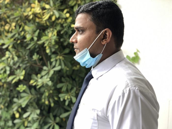 Portrait of young asian man with face mask standing outdoors