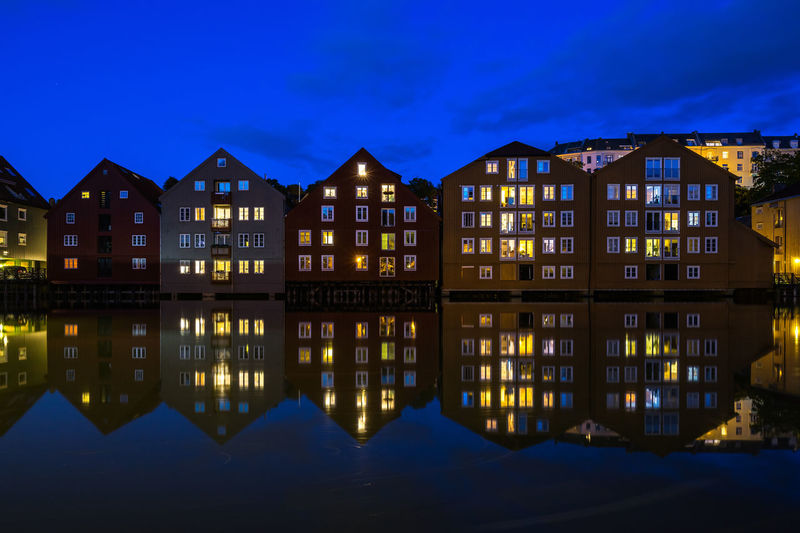 Blue hour view of old storehouses converted in residential buildings along the Nidelva River, Trondheim, Norway Trondheim Norway Scandinavia Norwegian Northern Europe Illuminated Architecture Night Built Structure Building Exterior Water Waterfront Reflection Sky No People Building Nature City Dusk House Residential District River Outdoors Blue Row House