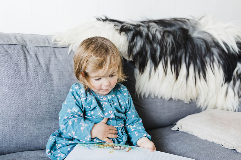 Toddler girl sitting on sofa and reading picture book - Hindeloopen, Friesland, Netherlands Baby Babyhood Beginnings Blond Hair Book Caucasian Close-up Comfortable Communication Confidence  Cozy Curiosity Discovery Domestic Room Education Fur Girl Girls Females Dress Well-dressed Hand Human Hand Happiness Happy Holding Home Individuality Home Interior Furniture Living Room Sofa Joy Kids Learning Looking Down Netherlands People Picture Book Playing Portrait Reading Reading A Book Relaxing Studying Waist Up Watching Toddler  Toddlerlife Talking Childhood Child One Person Innocence Sitting Indoors  Domestic Casual Clothing Real People Cute Front View Hair