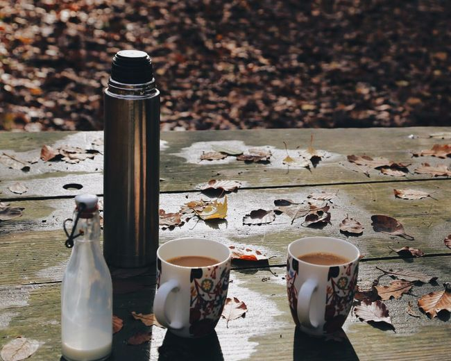 High angle view of insulated drink container with coffee and milk on table