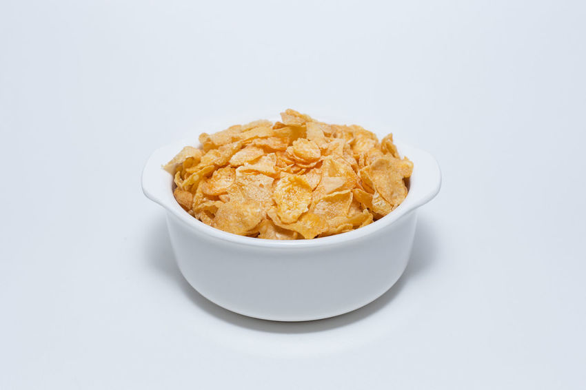 The image Close up Cornflakes cereal breakfast in white bowl on white background. CornflakesCrew Bowl Close-up Comfort Food Cornflakes Cornflakes & Coffee Flavors Cornflakes And Milk Day Food Food And Drink Freshness Healthy Eating No People Ready-to-eat Studio Shot White Background