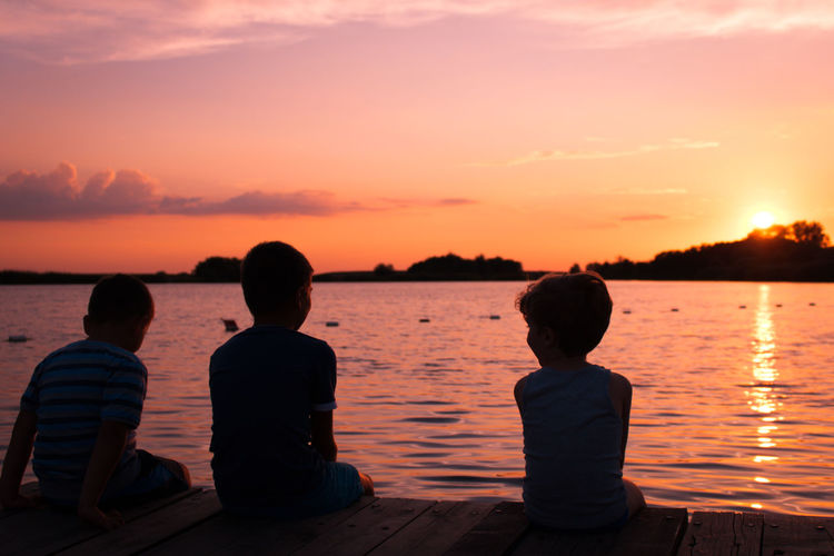 Rear view of boys sitting at beach against sky during sunset