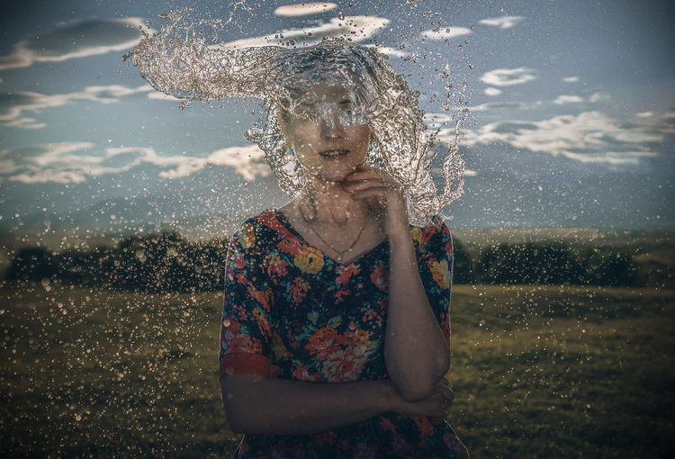 Water splashing on woman standing against sky