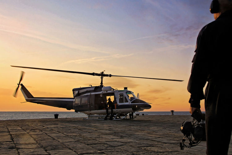 A helicopter department divers prepares for takeoff on the platform of an Italian port. Parking Aircrew Airplane Blades Cloud - Sky Departure Control Diving Dock Flying Hangarù Helicopter Horizon Over Water Military Outdoors Pilot Propellers Sailing Sea Silhouette Sky Sunset Sunset Silhouettes Surgery Takeoff ✈ Worker