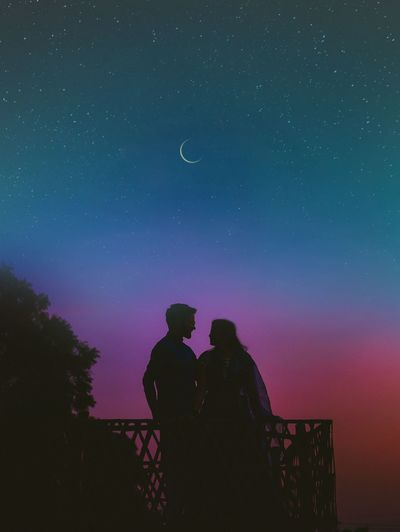 Silhouette man and woman standing against star field at night