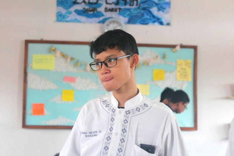 Boy Standing Against Blackboard In Classroom