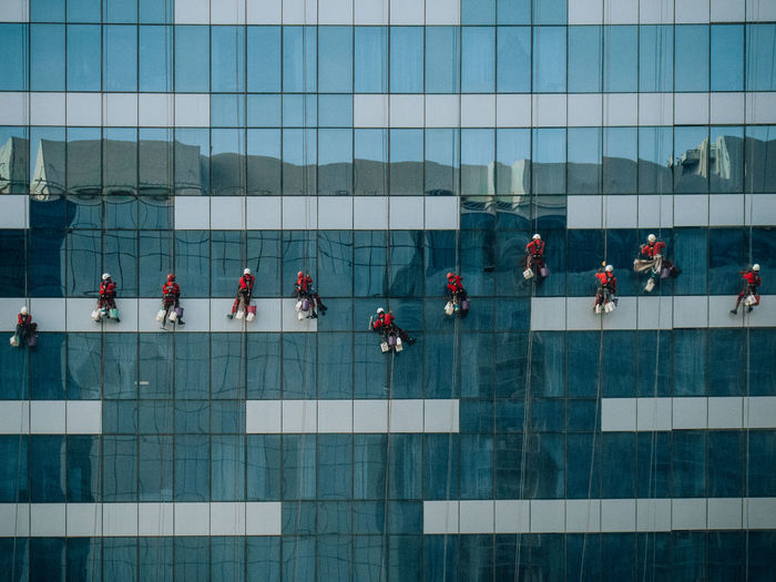Workers cleaning window of office building