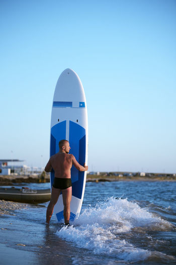 Rear view of shirtless male surfer holding surfboard at beach against clear sky
