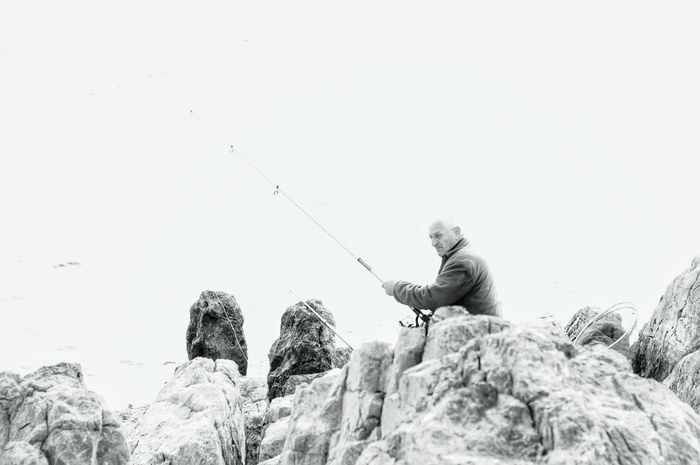 Overexposed People Of The Oceans One Man Only Outdoors Fisherman Outdoor Pursuit Lifeisbeautiful Old But Awesome Old Man Fishing Patience Fishing Pole Fishing Tackle Weekend Activities Blackandwhite Blackandwhite Photography Catch Of Fish Retirement Real People Nikon Nikonphotography Sea And Rocks Rock Formation Rocks The Human Condition