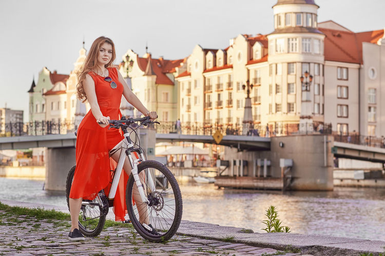 Full length of woman on bicycle in city