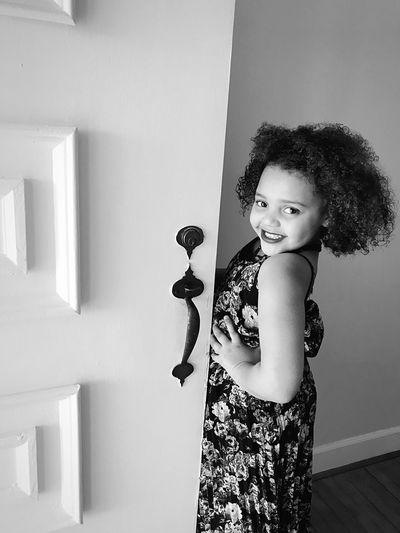 Portrait of smiling girl standing by door