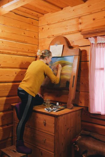 Rear view of woman drawing on canvas in cottage