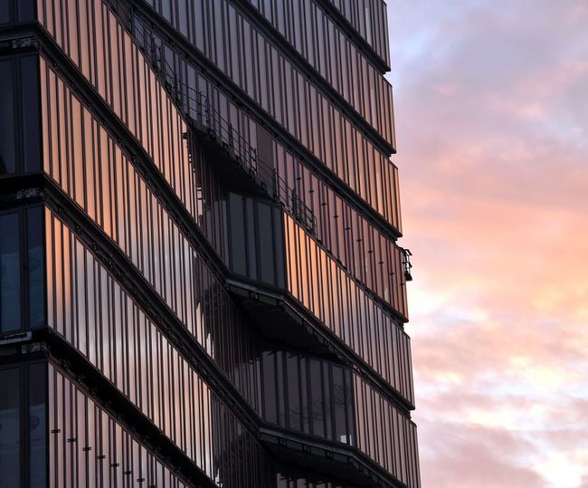 Low angle view of modern building against cloudy sky during sunset