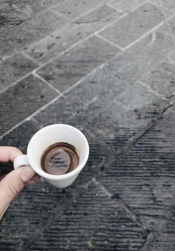 Cropped hand having coffee in cup at footpath