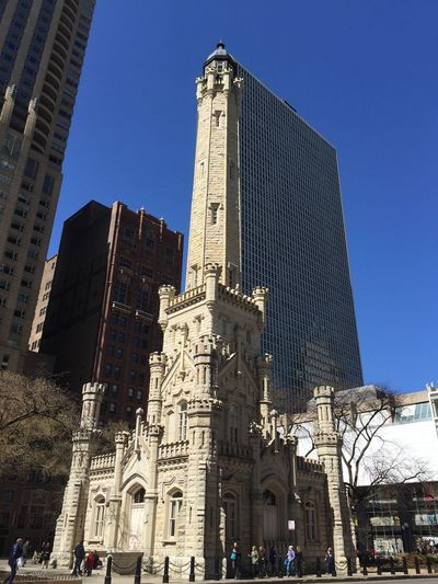 Low angle view of water tower place against clear blue sky in city