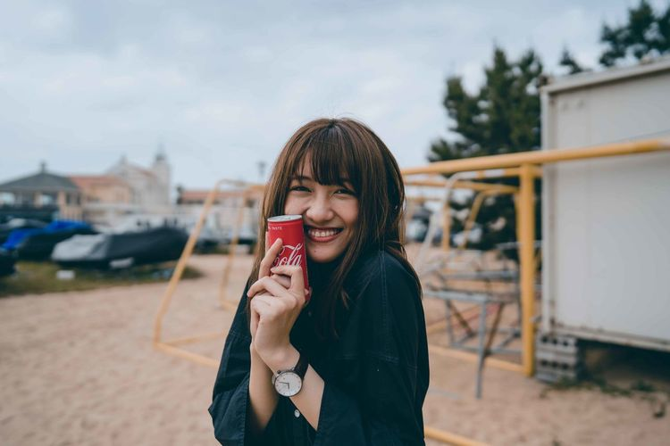 Portrait of smiling young woman holding camera while standing outdoors