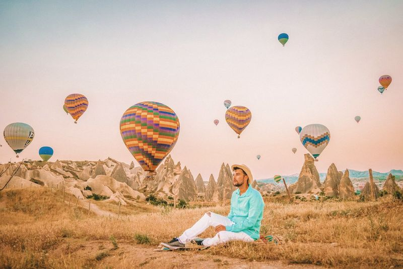 Thoughtful Mid Adult Man Sitting On Field Against Hot Air Balloons Flying In Mid-Air