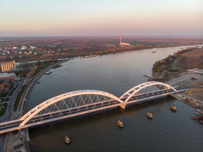 High angle view of bridge over river in city against sky during sunset
