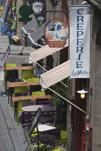 Creperie in Saint-Malo, Brittany, France Ancient Bistro Brittany Building Exterior Cafe Chair Crêperie Food Food And Drink France French Gastronomy Lifestyles Narrow No People Outdoors Pavement Pavement Cafe Restaurant Saint-Malo Sign Street Table Text Text