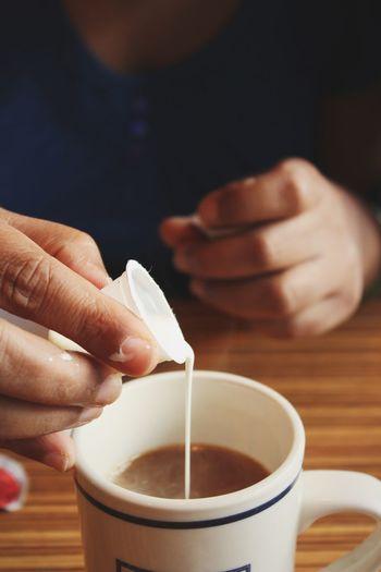 Person pouring milk into tea