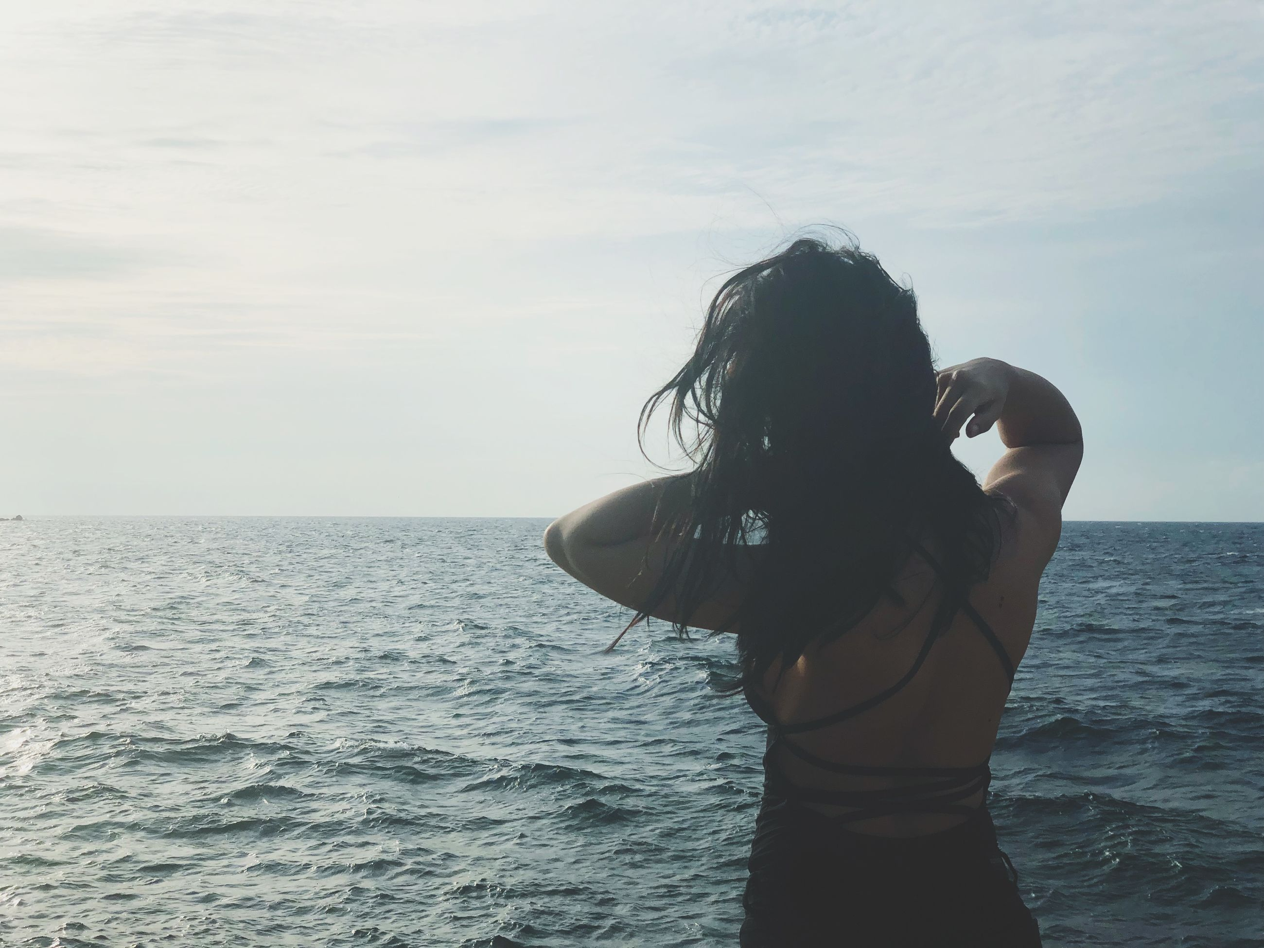 sea, water, sky, one person, horizon, real people, horizon over water, scenics - nature, beauty in nature, women, standing, lifestyles, leisure activity, young women, young adult, hair, nature, rear view, hairstyle, outdoors