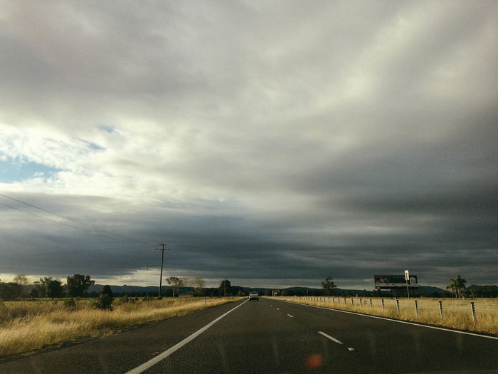 Highway against cloudy sky