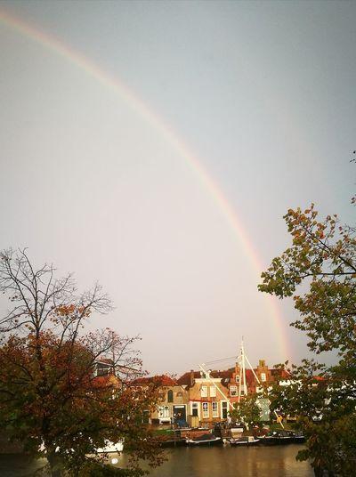 Rainbow over buildings against clear sky