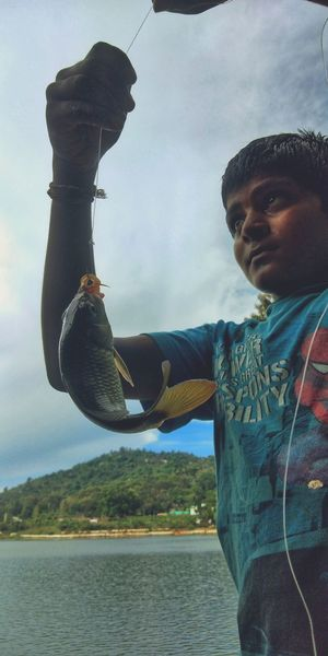 Man holding fish in lake against sky