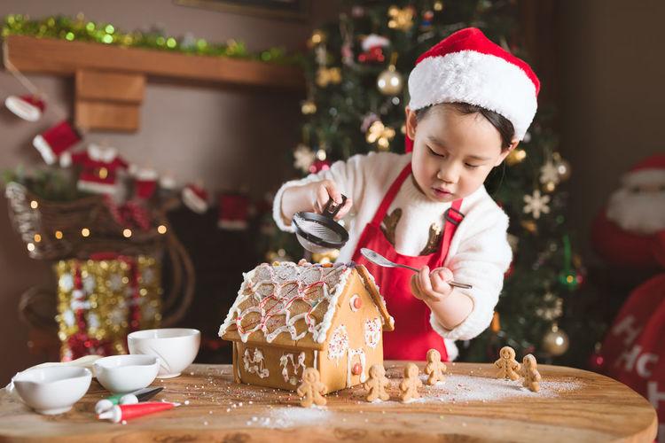 Cute girl preparing gingerbread house at home