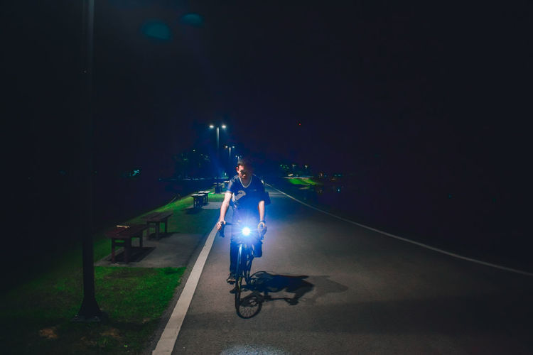 Man riding bicycle on road at night