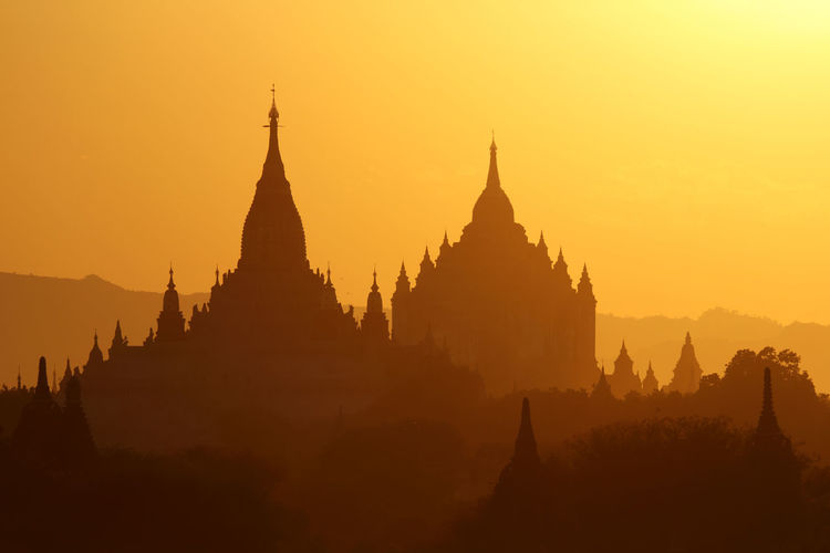 Silhouette temples against clear sky during sunset