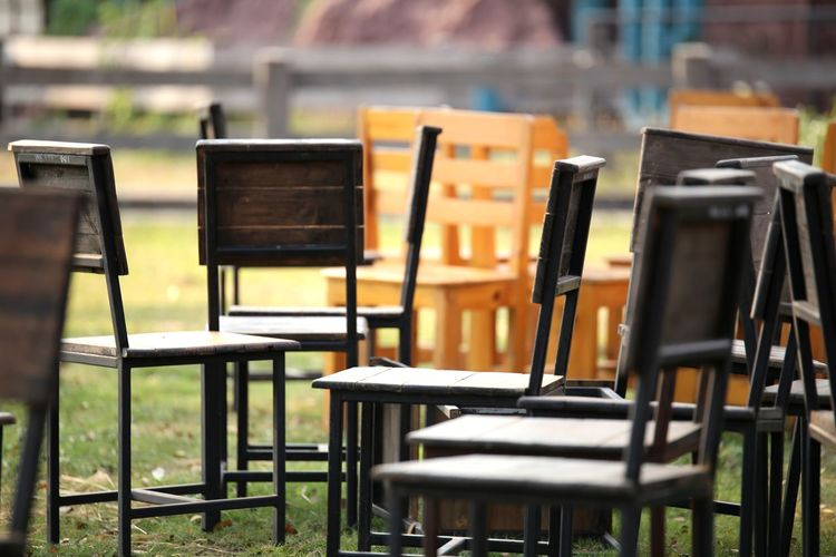 Empty chairs and tables at sidewalk cafe