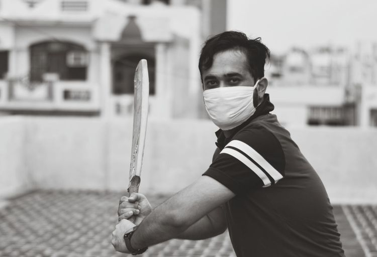 Portrait of young man standing outdoors wearing protective gear during quarantine time.