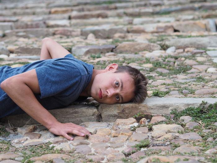 Portrait of man lying down on footpath
