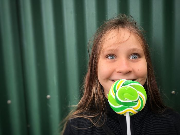 Young girl with a lollipop. Green Color One Person Childhood Portrait Looking At Camera Long Hair Real People Sweet Food People Sweet Candy Lolly Lollipop Treat Happy Happiness Joy Blue Eyes Girl Sommergefühle Human Connection Moments Of Happiness