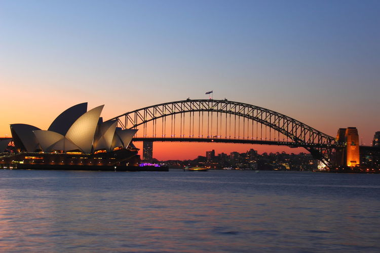 Opera house by harbor bridge at seafront during sunset