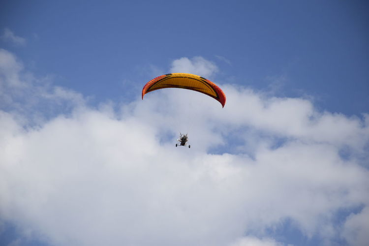 Low angle view of parachute flying against sky