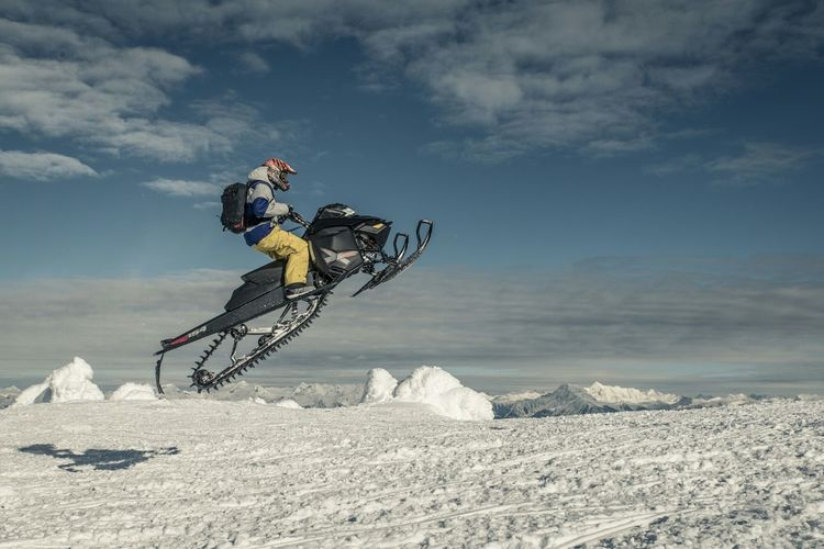 Side view of man snowmobiling on snowcapped mountain