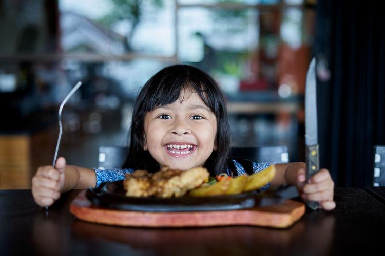 Portrait of smiling girl holding food