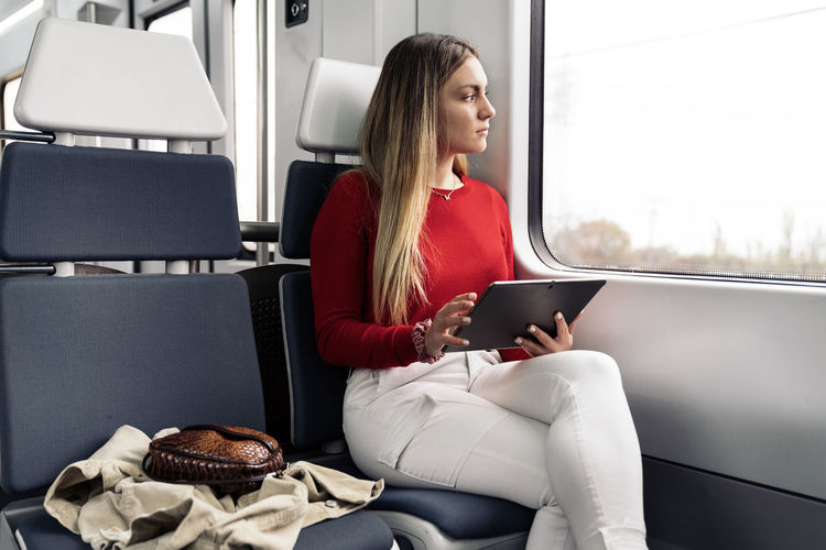Woman sitting on seat in bus