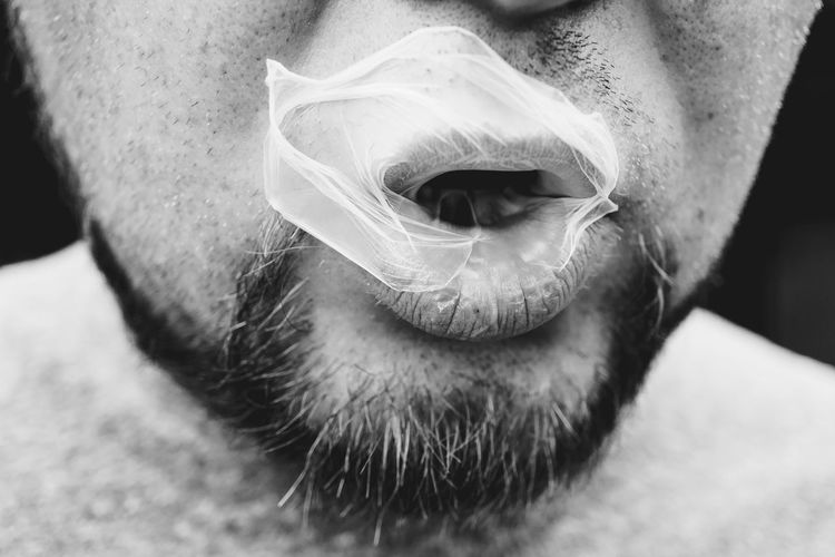Close-up of mid adult man blowing bubble gum